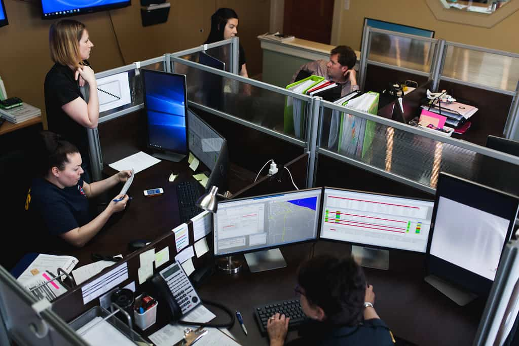 Office cubicles with computers and staff
